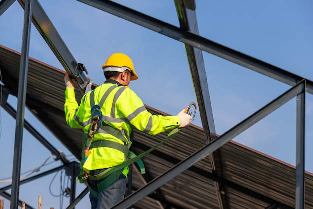 O trabalhador da construção de telhado asiático usa equipamento de segurança de altura para instalar a estrutura do telhado. dispositivo antiqueda para trabalhador com ganchos para cinto de segurança no canteiro de obras.