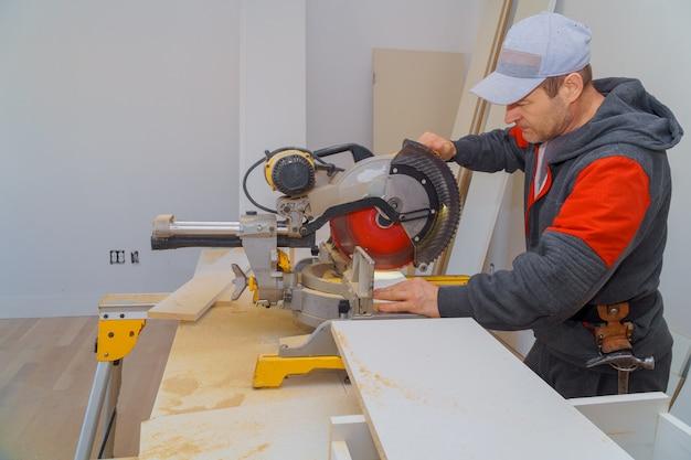 O trabalhador da construção que remodela a placa de madeira da guarnição do corte do carpinteiro sobre com viu.