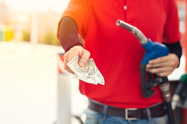 O trabalhador da equipe do posto de gasolina devolve o dinheiro para um preço mais baixo do combustível, redução dos custos do gás, redução do preço da gasolina para economia e conceito de reembolso em dinheiro