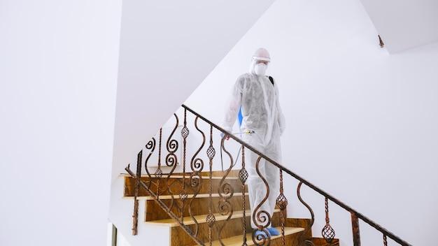 O trabalhador da linha de frente em traje anti-risco desinfeta a escada de bloqueio contra covid-19.