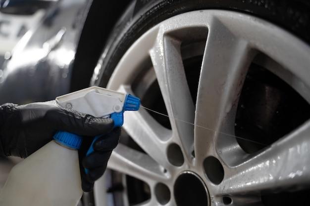 O trabalhador de detalhamento de automóveis aplica química às rodas.