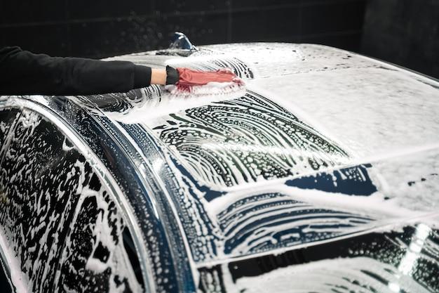 O trabalhador de detalhamento lava a carroceria do veículo com espuma e pano