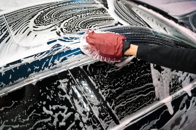 O trabalhador de detalhamento lava a carroceria do veículo com espuma