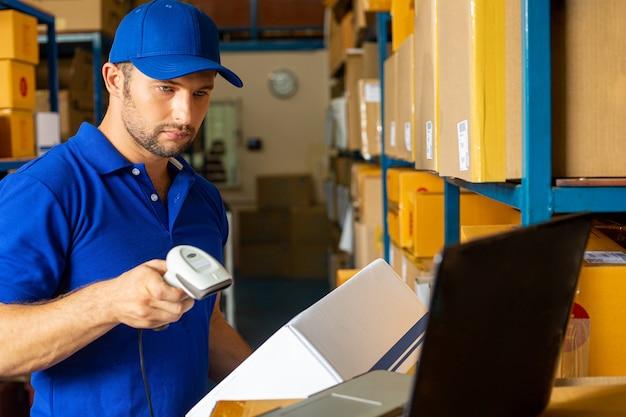 O trabalhador de entrega segurando a caixa para enviar ao cliente por cheque com scanner