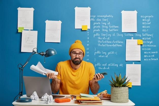 O trabalhador de escritório com barba duvidosa verifica os dados de trabalho dos papéis, prepara o relatório da empresa, segura o celular e o documento