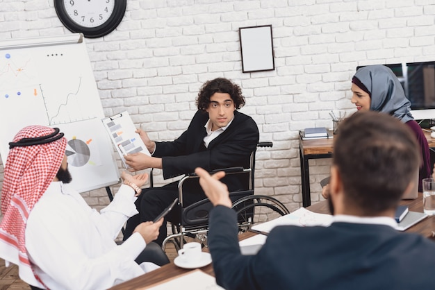 O trabalhador de escritório incapacitado fala os colegas para escutar.