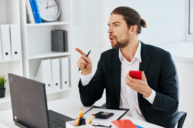 O trabalhador de escritório trabalha as emoções na frente do chefe de comunicação do laptop
