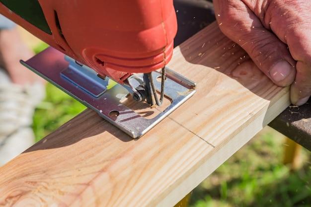 O trabalhador de madeira que corta o painel de madeira com gabarito viu ao ar livre