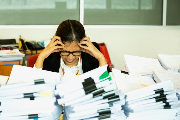 O trabalhador de mulher do escritório é afligido com muitos papéis em sua mesa.
