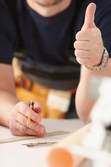 O trabalhador de sorriso na mostra amarela do capacete confirma o sinal com o polegar acima no retrato do braço. trabalho manual diy inspiração marcenaria startup idéia fixar loja capacete educação industrial profissão carreira conceito