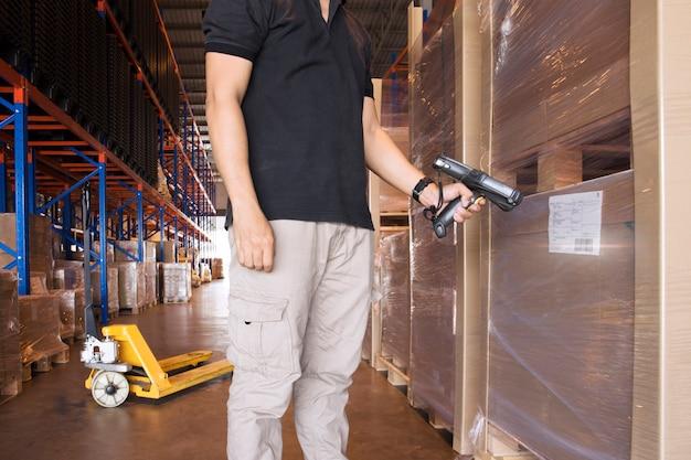 O trabalhador do armazém está guardando o varredor de código de barras com exploração nos produtos.