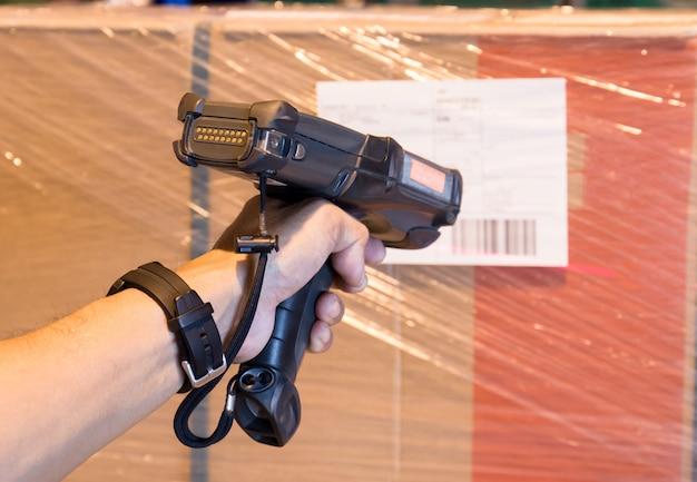 O trabalhador do armazém está segurando um scanner de código de barras com digitalização na expedição do produto.