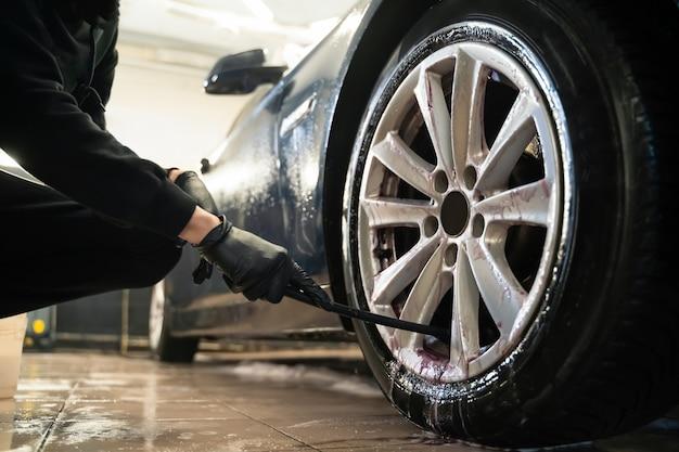 O trabalhador do centro de detalhamento limpa rodas de carro com pincel.