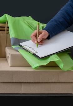 O trabalhador do serviço de entrega fica perto do local de trabalho com caixas e escreve no tablet.
