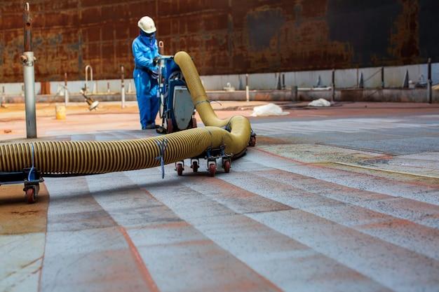 O trabalhador é remover o tanque do telhado de tinta por jato de areia de pressão de ar do motor do equipamento