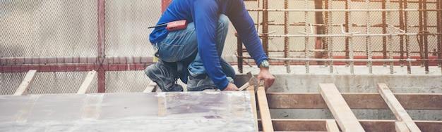 O trabalhador em azul sentado duro e trabalhando com canteiro de obras