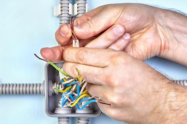 O trabalhador está apertando a fiação de cobre da caixa de junção para um bom contato.