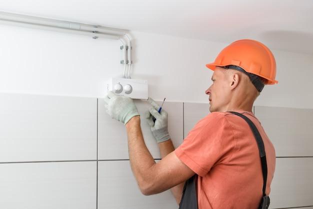 O trabalhador está conectando o sensor de umidade do sistema de ventilação.