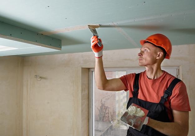 O trabalhador está enchendo as costuras das placas de gesso com massa de gesso