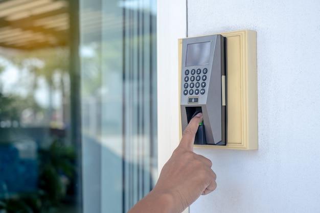 O trabalhador está escaneando os dedos para abrir a porta ou para marcar a hora do trabalho.
