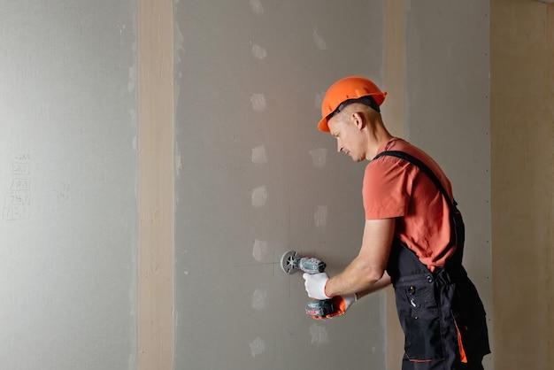 O trabalhador está fazendo furos na parede de gesso