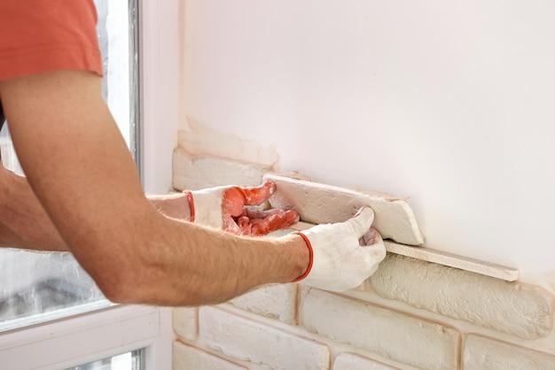 O trabalhador está instalando telhas de tijolo de gesso na parede.