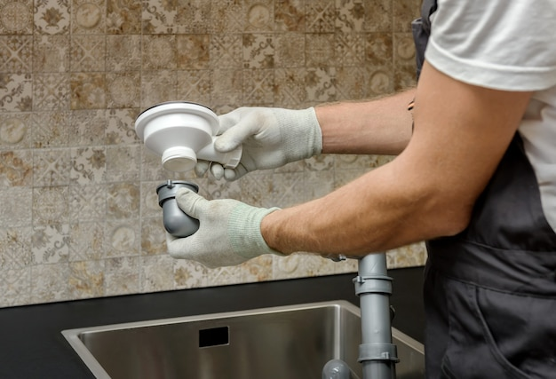 O trabalhador está instalando um ralo de esgoto para a pia da cozinha.