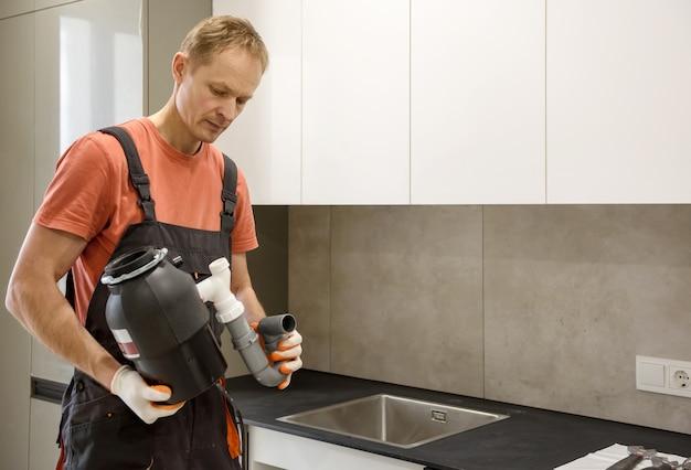 O trabalhador está instalando uma trituradora de lixo doméstico para a pia da cozinha.