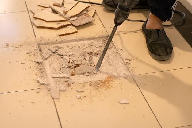 O trabalhador está removendo as telhas quebradas para reparo.