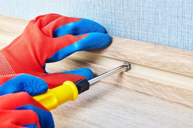 O trabalhador está torcendo o parafuso no canal a cabo do rodapé do piso por uma chave de fenda.