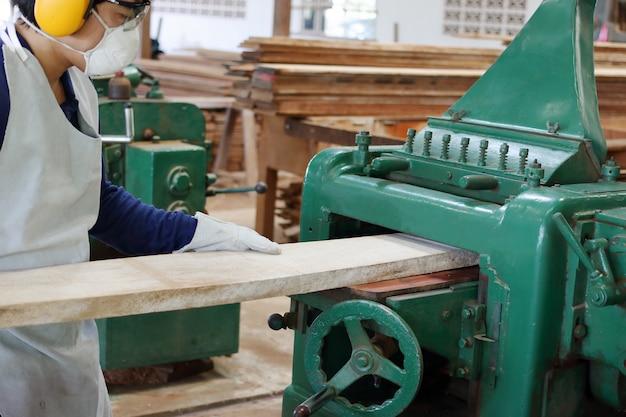 O trabalhador está trabalhando com aplainamento de máquinas de madeira. ele está usando equipamento de segurança na fábrica
