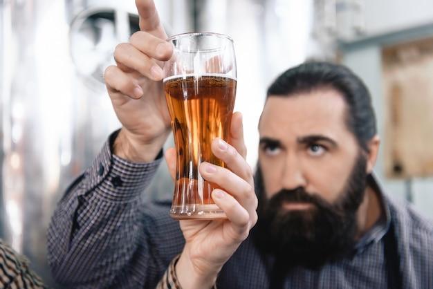 O trabalhador farpado concentrado verifica a cor da cerveja inglesa.