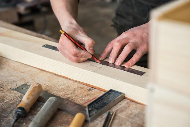 O trabalhador faz medições de uma placa de madeira