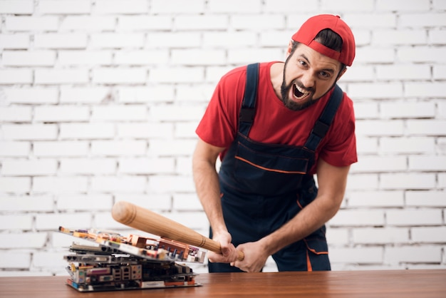 O trabalhador forçado arruina placas de pc com bastão de beisebol.