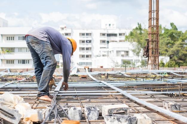 O trabalhador instala o fio no assoalho da construção para a torre sob o canteiro de obras.