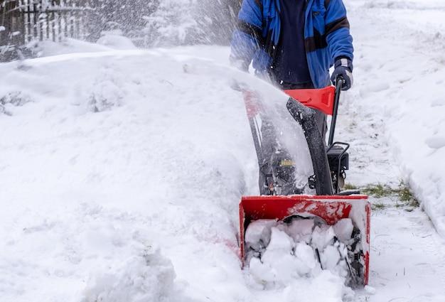 O trabalhador limpa ruas ou quintais de neve com um soprador de neve no inverno