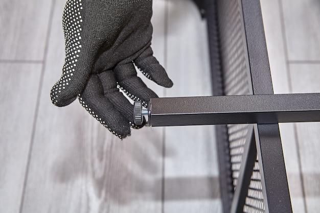 O trabalhador manual ajusta a altura da perna da mobília da embalagem plana.