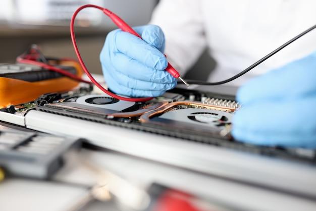 O trabalhador manual com luvas repara a placa-mãe. manutenção e reparo do conceito de equipamentos de informática