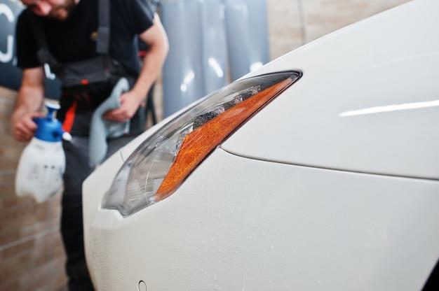 O trabalhador no detalhamento da garagem colocou uma capa de filme anti-cascalho de poliuretano em um carro branco de luxo.