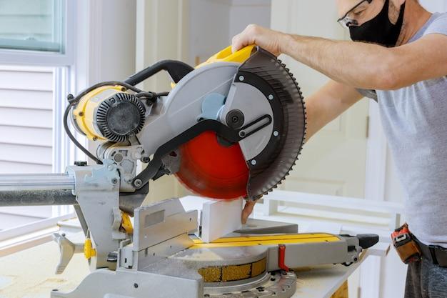 O trabalhador protege-se da covid-19, homem cortado usando serra circular serra rotativa cortando rodapé de madeira
