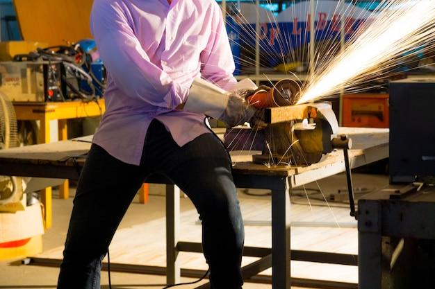 O trabalhador usa máquina de corte para cortar metal, foco na linha de luz de flash de faísca afiada, em baixa luz