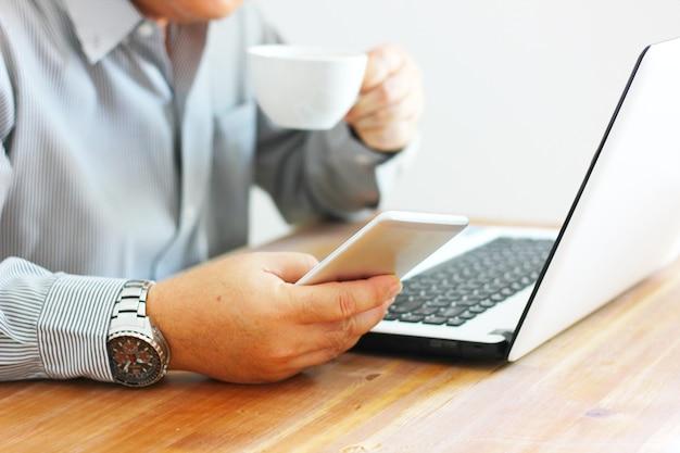 O trabalhador usando o celular pesquisando informações enquanto bebe café e procura o laptop na mesa