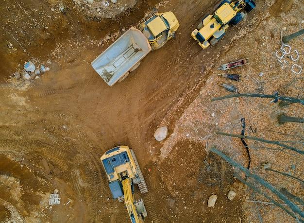 O trabalho de equipamentos de construção na produção de terraplenagem em escavadeiras de caminhões basculantes com em construção