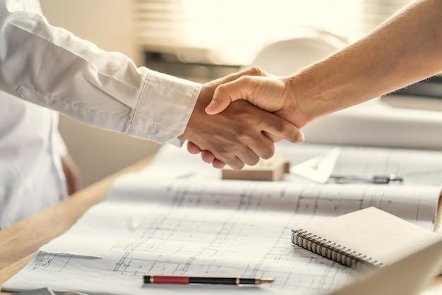 O trabalho de equipe de oficial está feliz e aperta as mãos para celebrar em sucesso do fim em um trabalho que planeja sobre um projeto de construção de edifício de casa