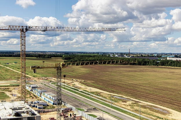 O trabalho de guindastes de torre no contexto do céu do sol. construção de moradias modernas. engenharia industrial. construção de hipotecas de habitação.