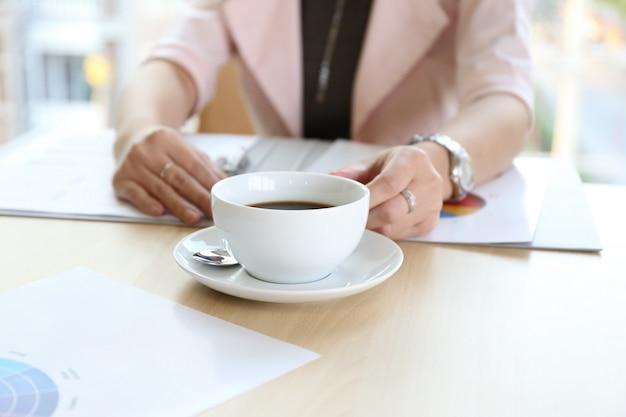 O trabalho de mão esperto chique asiático da mulher bronzeado bonita encantador da pele no telefone do portátil e escreve a pena na leiteria do caderno na tabela de madeira no escritório. apresentando seu produto com desempenho bom trabalho da mulher.