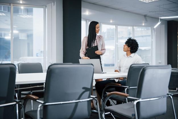 O trabalho de rotina não é chato para essas pessoas. profissionais jovens. colegas de trabalho alegres em um escritório moderno, sorrindo ao fazer seu trabalho usando laptop