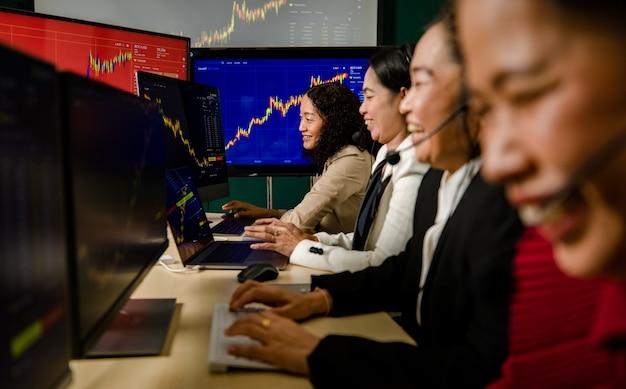 O trabalho em equipe de mulheres felizes, operadores de marketing comercial, usa fone de ouvido com microfone, sente-se sorrindo, fazendo bitcoin criptomoeda na bolsa de valores, compra e venda de transações comerciais do monitor gráfico gráfico no escritório.