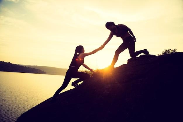 O trabalho em equipe de trabalho conjunto de duas pessoas esporte menina ajuda uns aos outros no topo de uma montanha cli