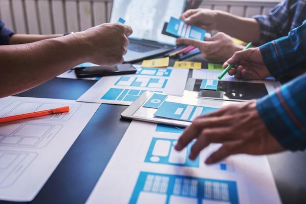 O trabalho em equipe do design gráfico da experiência do usuário móvel ajuda a projetar um novo emprego no escritório moderno. conceito de trabalho em equipe freelancer de estilo de trabalho de design.